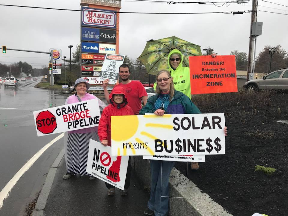 image shows six individuals standing on a street with raincoats on and signs about solar energy's importance and stopping the Granite Bridge pipeline